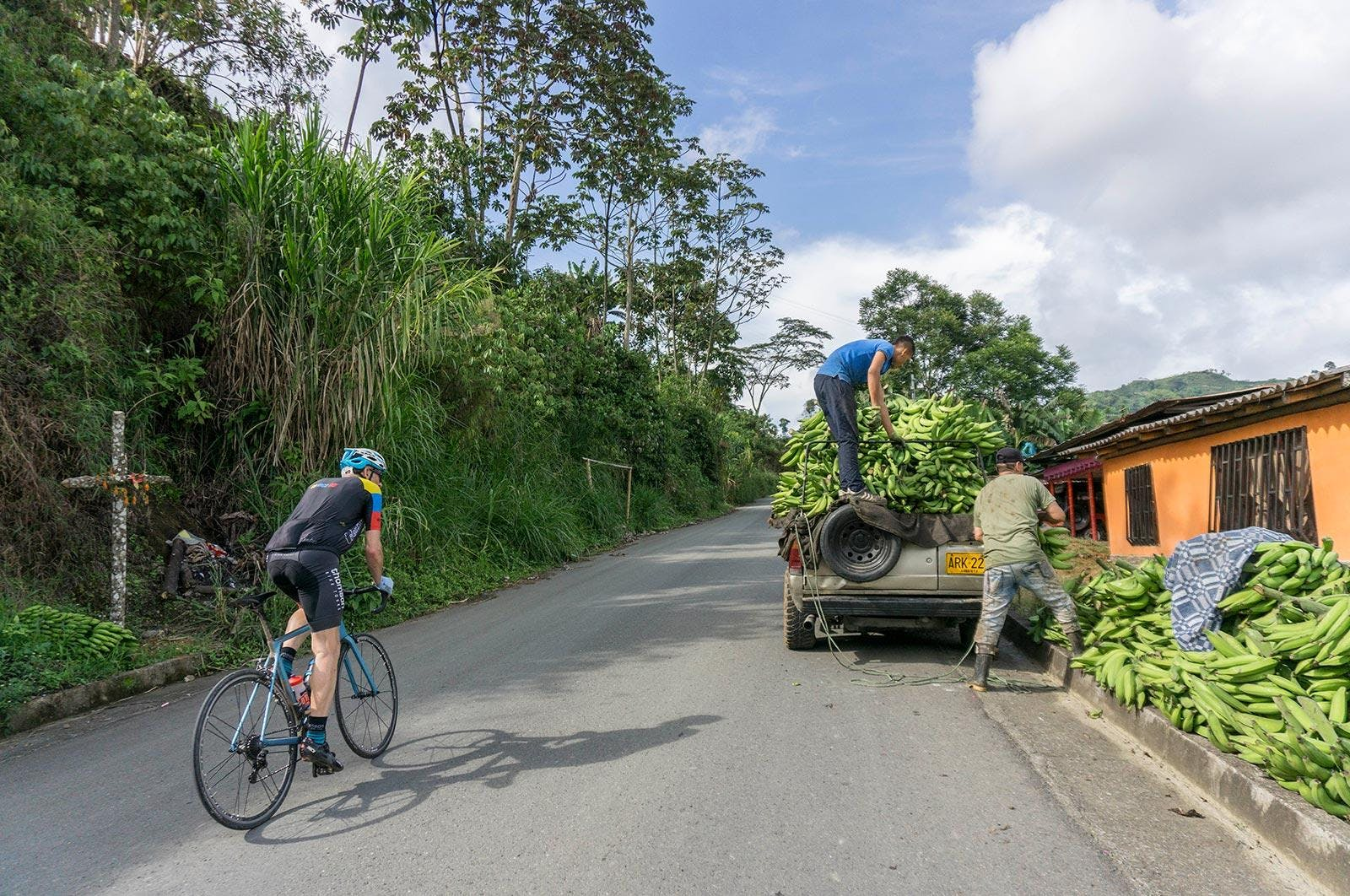 Thomson bike tours in Colombia, cycling past some banana farmers